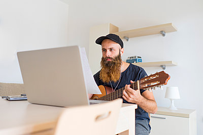 Serious young man at home with earphones and laptop playing guitar - p300m1580788 von VITTA GALLERY