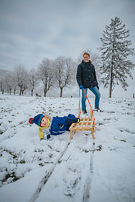 Son falling off a sledge while being pulled by father in snowy landscape, Blankenheim, NRW, Germany - p300m2266927 von Mareen Fischinger