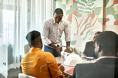 Young male architect explaining architectural model to coworkers during meeting at office - p300m2283018 by Zeljko Dangubic