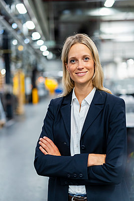 Female manger standing with arms crossed at industry - p300m2299116 by Daniel Ingold