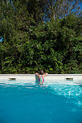 Girl resting at the poolside - p954m1585913 by Heidi Mayer