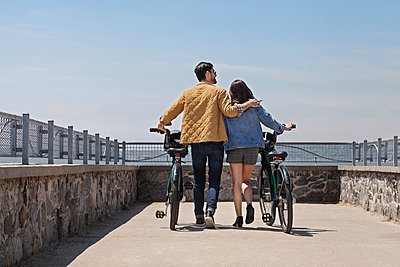 Rear view of couple with Citi Bikes walking at observation point against clear sky - p1166m1533653 by Cavan Images