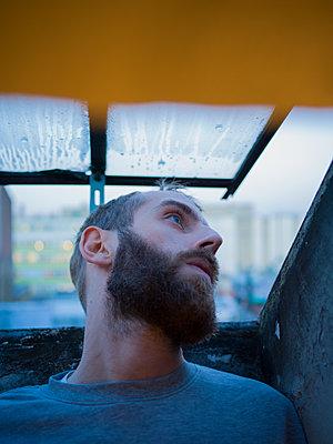 Man in front of open attic window - p1267m2064774 by Wolf Meier
