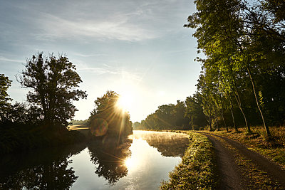 River with path and trees in the backlight - p1312m2263122 by Axel Killian