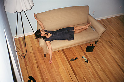 Woman relaxing on sofa in NYC loft - p1614m2185791 by James Godman