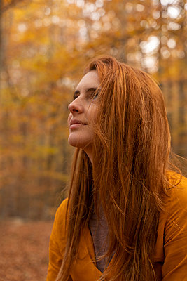 Portrait of redheaded young woman in autumnal forest - p300m2159843 von VITTA GALLERY