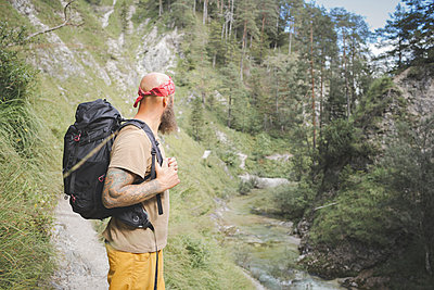 Mature man with backpack standing against trees in forest, Otschergraben, Austria - p300m2221365 by Epiximages