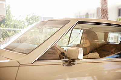 Beautiful woman driving car in city - p300m2224968 by LOUIS CHRISTIAN
