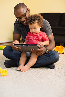 Father and toddler son using digital tablet - p555m1459378 by Roberto Westbrook
