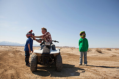 Father and sons on four-wheeler - p924m768495f by Raphye Alexius