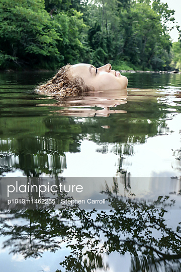 Female teenager floating in water - p1019m1462255 by Stephen Carroll