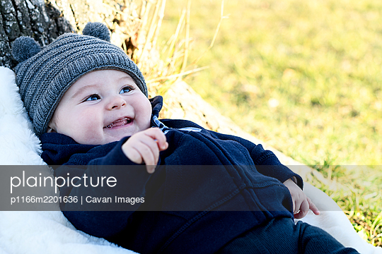 A few months old baby laughing in the park with a wool cap on - p1166m2201636 by Cavan Images