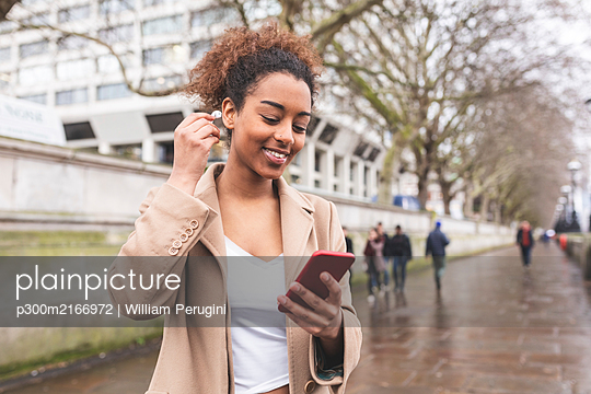 Smiling young woman with cell phone and earbuds in the city, London, UK - p300m2166972 by William Perugini