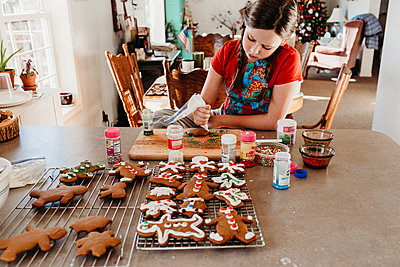 Girl Decorating Christmas Cookies with Icing and Sprinkles - p1166m2162554 by Cavan Images
