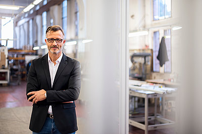 Portrait of smiling mature businessman in factory - p300m1562719 by Daniel Ingold
