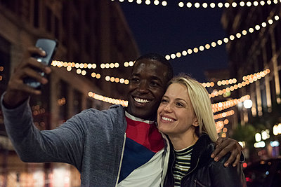 Happy young man with girlfriend taking a selfie at night - p300m2013185 by Westend61