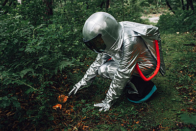 Spaceman exploring nature, examining plants in forest - p300m2030495 by Vasily Pindyurin
