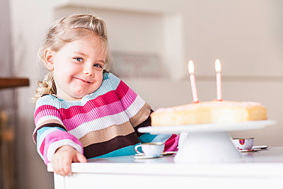 Smiling girl sitting at table with birthday cake - p300m2189484 by Floco Images