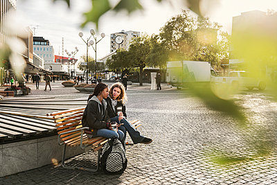 Teenage girl sitting on bench - p352m2121179 by Folio Images