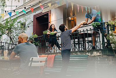 Young man giving food to male friend from balcony during garden party - p426m2046219 by Maskot