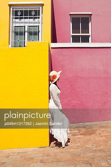 Frau an bunte Häuserwand angelehnt - p045m1217352 von Jasmin Sander
