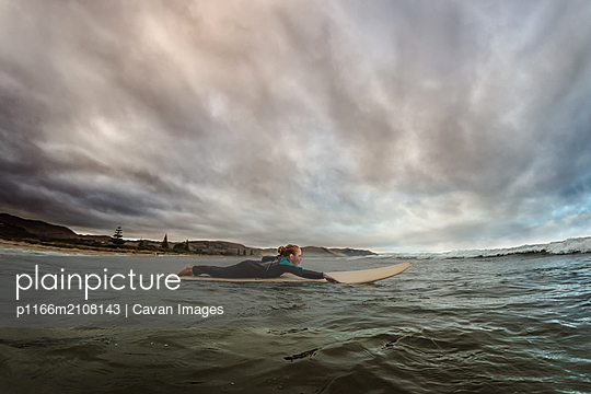 Adolescent girl paddling on a surfboard at dusk in the ocean - p1166m2108143 by Cavan Images