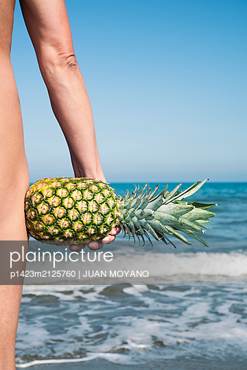 Nude man with a pineapple in his hand on the beach - p1423m2125760 von JUAN MOYANO