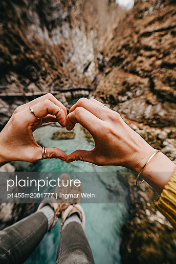 Person forming a heart with her hands with the Vintgar Gorge in Slovenia in the background - p1455m2081777 by Ingmar Wein