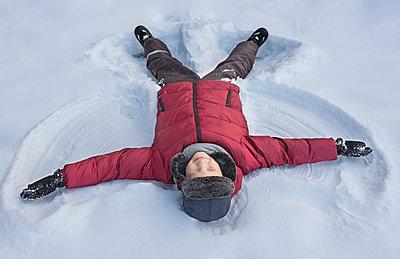 Boy making snow angel - p1427m2067343 by Valeriya Tikhonova