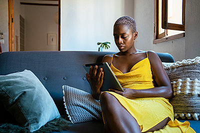 Woman using digital tablet while sitting on sofa at home - p300m2241635 by Rafa Cortés