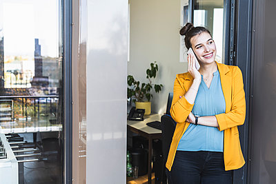 Businesswoman talking on mobile phone while standing at door in office - p300m2241702 by Uwe Umstätter
