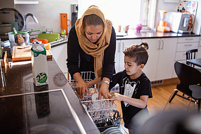 Mother and son arranging utensils in dishwasher at kitchen - p426m1193031 by Maskot