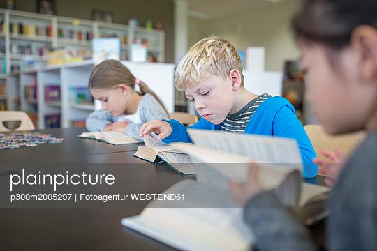 Pupils reading books on table in school break room - p300m2005297 von Fotoagentur WESTEND61