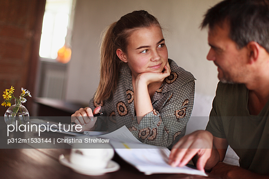 Father helping daughter with homework - p312m1533144 by Christina Strehlow