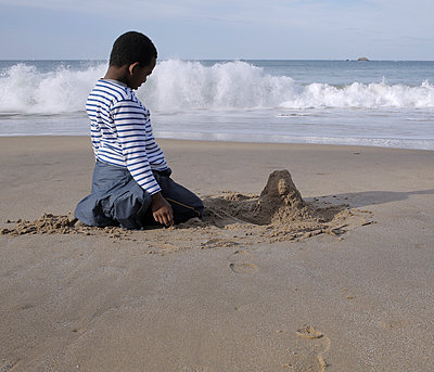Boy sitting in front of his sand castle - p1307m2257664 by Agnès Deschamps