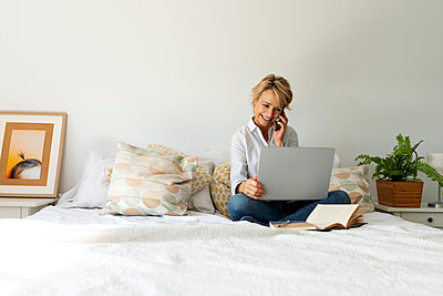 Mature woman sitting on bed at home using smartphone and laptop - p300m2144939 by Valentina Barreto
