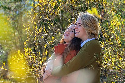 Smiling lesbian couple embracing amidst plants during sunny day - p300m2276071 by Lisa und Wilfried Bahnmüller