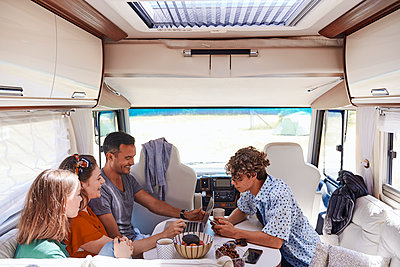 High angle view of family looking at laptop while sitting in camper van - p426m2046403 by Maskot