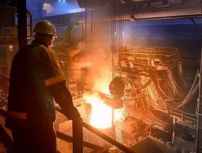 Steel worker inspecting pouring molten steel - p429m1013890f by Monty Rakusen