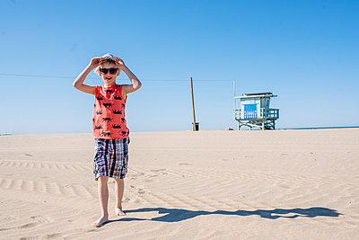Boy on sunny sandy beach, wearing sunglasses and hat - p924m2271142 by Viara Mileva