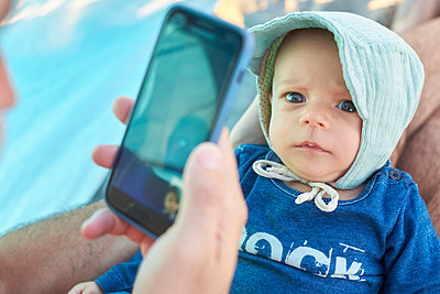 Baby with blue eyes, father using smarphone - p1146m2150567 by Stephanie Uhlenbrock