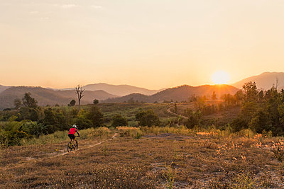 High angle view of man mountain biking on field against sky during sunset - p1166m1509355 by Cavan Images