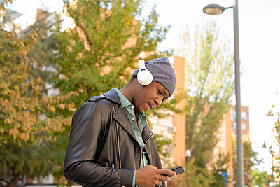 young african man in the city listening to music from his mobile phone - p1166m2218268 by Cavan Images