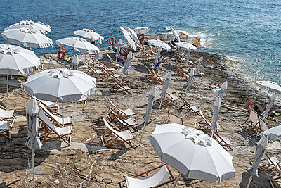 Holidaymakers under parasols on the waterfront - p1292m2126986 by Niels Schubert