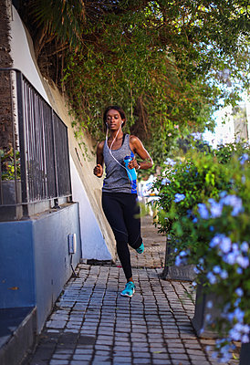 Young female runner listening to earphones running up city sidewalk - p924m2090581 by Bean Creative