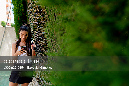 Woman using smart phone while standing by fence in sports court - p300m2213954 by Ezequiel Giménez