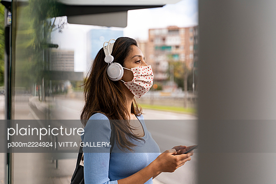 Contemplating woman in face mask wearing headphones with smart phone at bus stand during COVID-19 - p300m2224924 by VITTA GALLERY