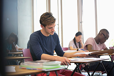University student taking exam, students in background writing - p1023m987106f by David Schaffer