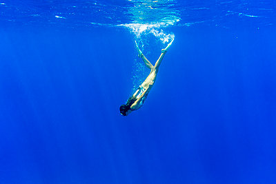 Young woman swimming underwater in sea - p1166m1174118 by Cavan Images