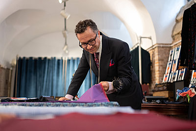 Mature tailor inspecting cloth in studio - p1166m2261407 by Cavan Images
